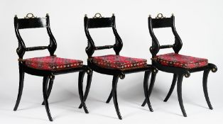 A set of six Regency style ebonised gilt metal mounted dining chairs, with rope-twist bar backs,