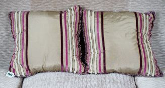 A pair of gold silk cushions with raised velvet bands (2).