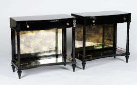 A pair of ebonised bowfronted console tables, in Empire style, with frieze drawers,