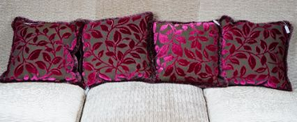 A set of four grey and magenta cut velvet cushions.