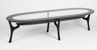 A black lacquered oval 'racetrack' coffee table, with glass inset top and undertier,