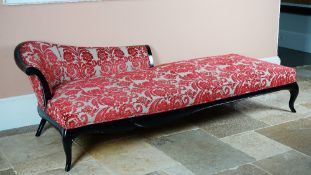 A large ebonised chaise longue, with shaped back and stuff-over seat, on cabriole legs,