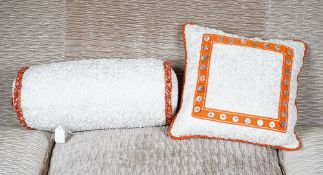 A scrunched cream silk bolster cushion, with braided ends,