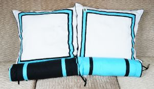 A set of four white cushions, with blue and black bands and four corresponding bolsters (8).