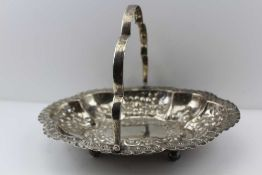 THOMAS LEVESLEY AN EDWARDIAN SILVER SWING HANDLED BASKET of embossed oval shaped form, on ball feet,