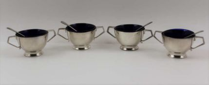 A SET OF FOUR EDWARDIAN SILVER SALTS of circular two handled design, fitted blue glass liners,