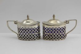 A PAIR OF GEORGIAN DESIGN SILVER MUSTARD POTS, hinged covers and pierced oval bodies, Chester