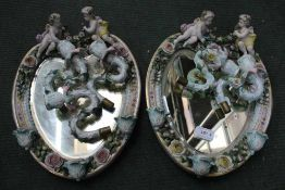 A PAIR OF PROBABLE CONTINENTAL FLORAL ENCRUSTED HANGING HEART SHAPED MIRRORED BACK SCONCES