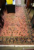 A LARGE PINK GROUND FLORAL DECORATED WOVEN WOOLEN FLOOR CARPET
