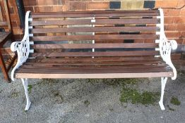A WHITE PAINTED CAST METAL FRAMED SLATTED GARDEN TWO-SEATER BENCH together with two slatted single