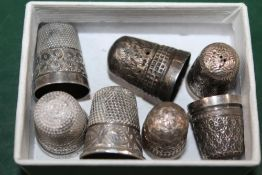 A SMALL BOX CONTAINING SILVER THIMBLES