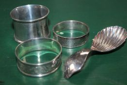 THREE HALLMARKED NAPKIN RINGS together with a silver scalloped bowl, tea caddy spoon