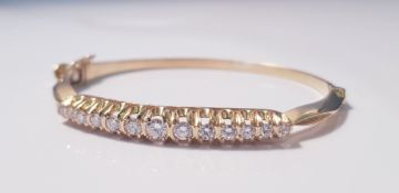 A yellow metal and diamond bangle, 13 diamonds to bangle, approx. weight 21gms. IMPORTANT: Online