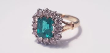 A yellow gold emerald and diamond square cluster ring, marked 750 , 12 diamonds surrounding emerald,