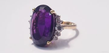 A yellow gold marked 750, amethyst and diamond cluster ring, with five small diamonds either side of