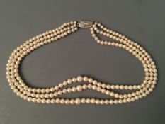 A three row string of pearls, 'Ledawn' with gem stone clasp marked sterling silver. IMPORTANT: