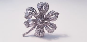 A diamond set flower design brooch, the open metalwork flower set with variously sized round