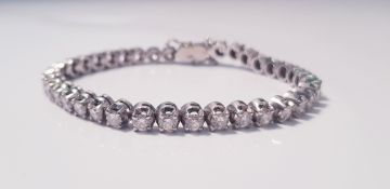 A tennis bracelet of approx. 38 diamonds, each diamond approx. 0.15ct, 750 marked on clasp,