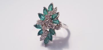 A white metal emerald and diamond dress ring, with twelve diamonds and ten emeralds, ring size L 1/