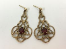 A pair of 9ct yellow gold and red gemstone dropper earrings stamped 375, approx. weight 3.8gms.