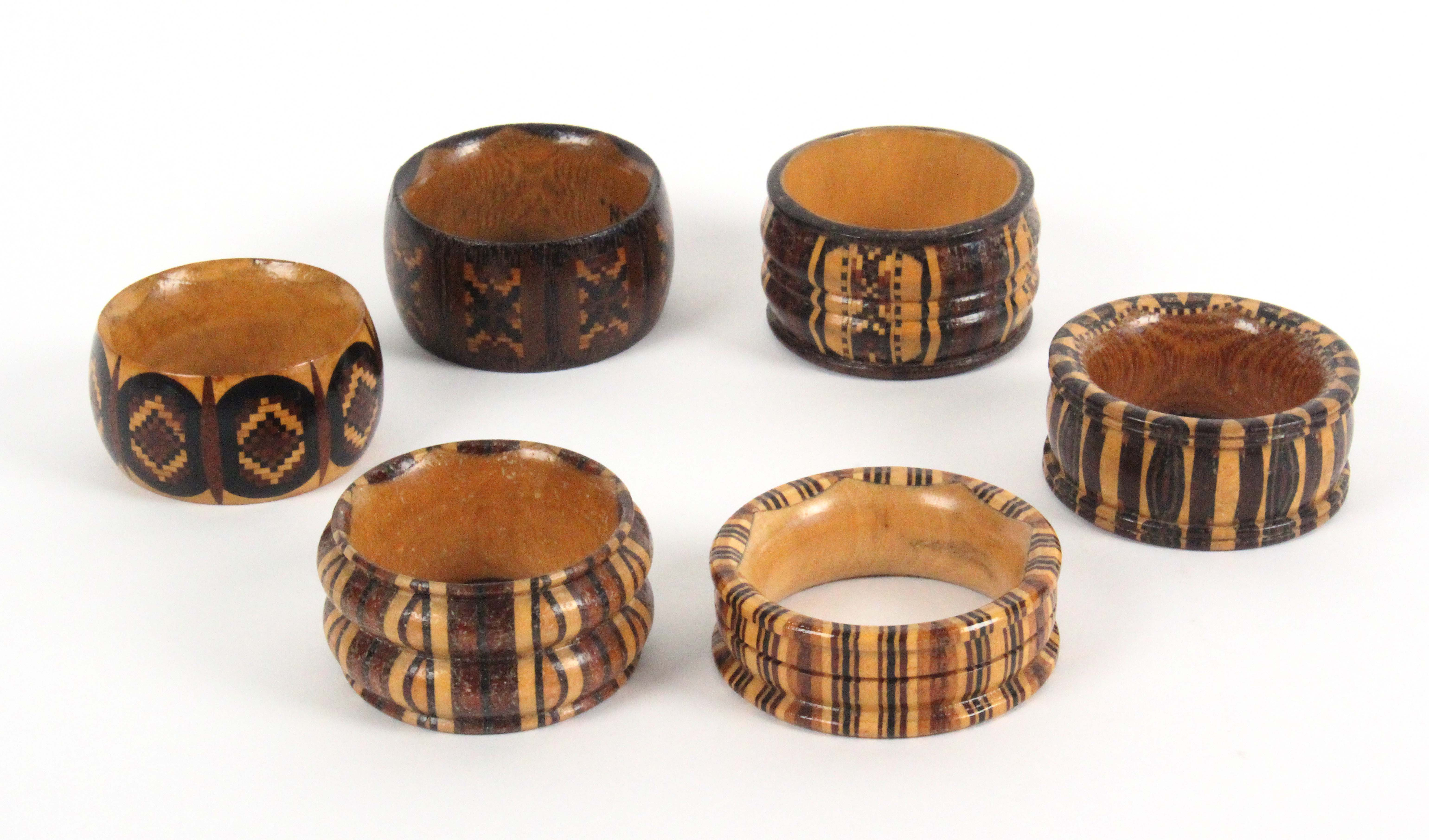 Lot 23 - Six variant Tunbridge ware napkin rings, in stickware and mosaic one with bone inset numeral, one