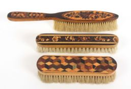 Three Tunbridge ware brushes, comprising an example in cube work, 16cm, another in mosaic, 17cm, and