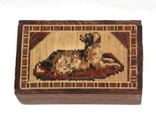 A Tunbridge ware mosaic block depicting a dog at rest within a geometric border, 7 x 4.2cm.