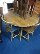 An Ercol Golden Dawn table and four Ercol spindle back chairs
