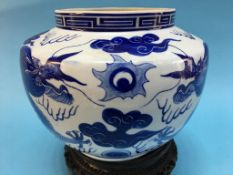 A Chinese blue and white vase, decorated with dragons, on carved hardwood stand