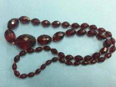A faceted red amber coloured necklace