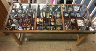A small coffee table, the top with small pigeon holes filled with costume jewellery, fossils,