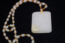 Large carved white jade pendant suspended on a bea