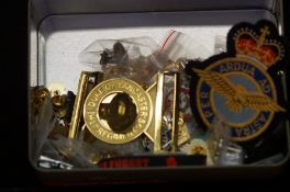 A large collection of military badges, belt buckle