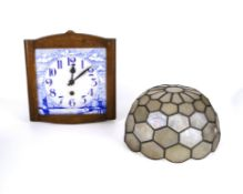 A blue and white pottery wall clock and a light shade