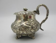 A George IV silver mustard pot by Joseph Biggs, London 1825, of bulbous form with embossed foliage