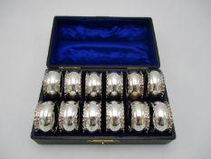 A cased set of twelve Edwardian silver napkin rings by C.T Burrows & Sons, Birmingham 1905, designed