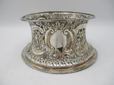A large white metal potato ring, of circular form with pierced repousse decoration throughout