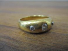 A gold coloured metal gypsy ring set with three diamonds, 9.5g