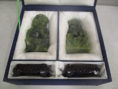 A pair of late 20th Century Chinese jade coloured Foo dogs, on stands boxed