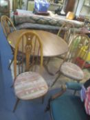 An Ercol Golden Dawn extending dining table, together with four Quaker Swan chairs