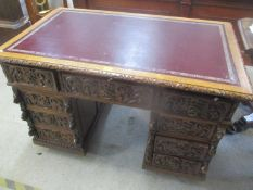 A late Victorian carved pussy oak twin pedestal desk having a leather topped scriber and nine