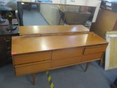 A mid 20th century teak retro dressing table having nine drawers and tapering legs