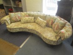 A bespoke made curved button upholstered sofa, on turned mahogany finished legs, 65cm high x 250cm