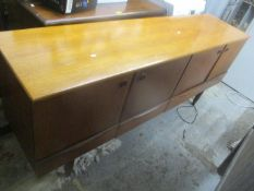 A mid 20th century retro teak sideboard having a fall flap flanked by two cupboard doors, 78.5h x