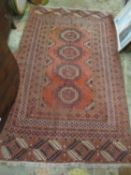 A Bokhara red ground rug having multi-guard borders and tasselled ends, 203cm x 121cm