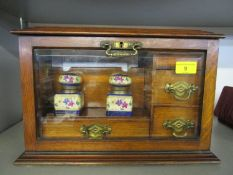 A Victorian oak stationery box with hinged lid and glazed fall front, fitted interior with three