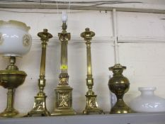 A brass column table lamp, a pair of brass column candlesticks and two oil lamps with shades A/F