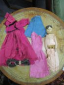 A 19th century Grodnertal wooden peg doll with dresses and undergarments