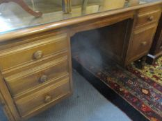 An Ercol twin pedestal desk housing a file drawer and four short drawers together with an Ercol