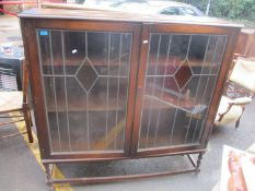 A 1930's oak bookcase with a pair of lead glazed doors on barley twist legs, 138 h x 137cm w